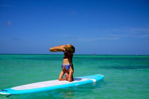 Yogalehrerin Rachel Brathen auf ihrem Surfbrett vor der Karibikinsel Aruba