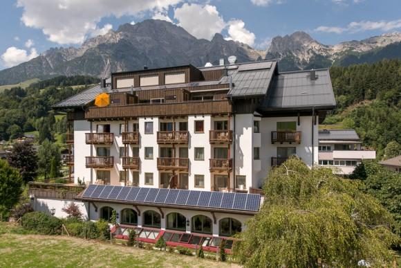 Hotel Der Löwe Aussenansicht im Sommer mit Bergpanorama im Hintergrund.