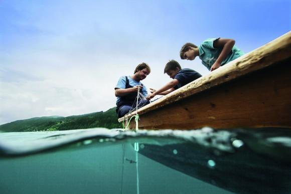 Während der Fischer gemeinsam mit seinen Gästen Reinanken und Hechte aus der Tiefe hebt, erzählt er Geschichten und Anekdoten rund um die Fischereitradition. Foto: Kärnten Werbung, Sam Strauss