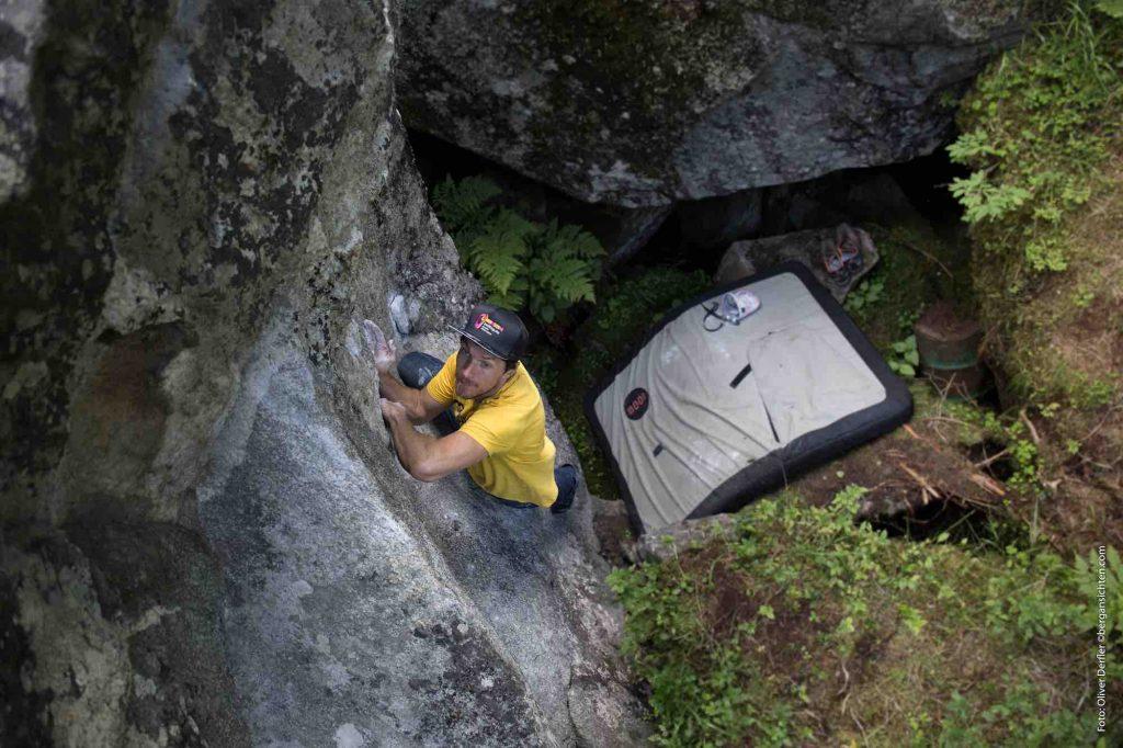 Kletterbares Maltatal - ein Boulderer von oben auf einem Steinblock über einem moosigen Waldboden