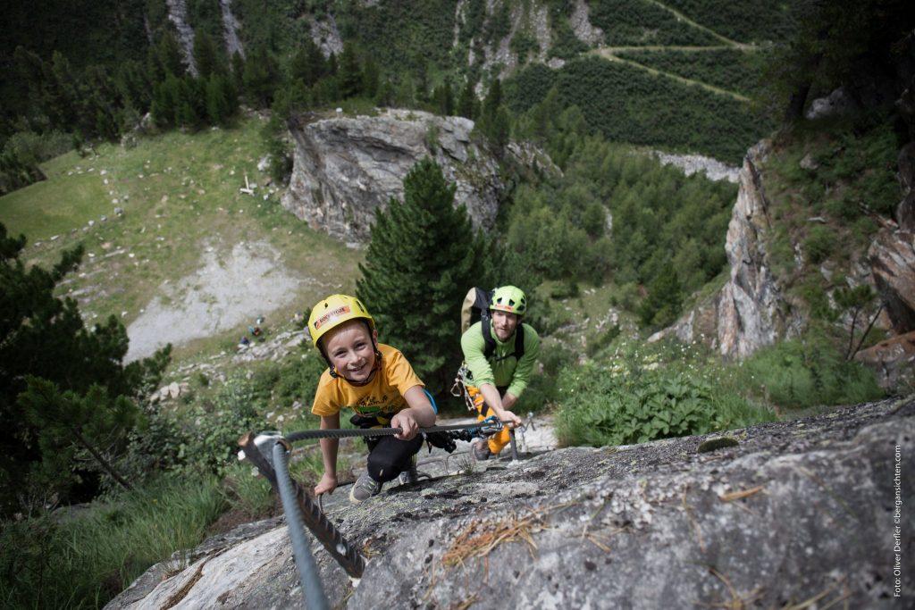 Kletterbares Maltatal - ein Kind mit seinem Vater im Klettersteig über einem alpinen Talboden