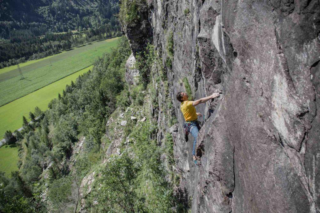 Kletterbares Maltatal - ein Kletterer hängt in einer schwarzen Felswand oberhalb einer grünen Wiese im Maltatal